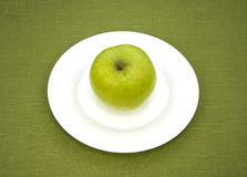 Apple on white plate Royalty Free Stock Photo