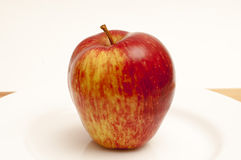 Apple on a white plate. 1 apple on a white plate on a cutting board Royalty Free Stock Image