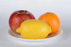 Apple wih orange and lemon. On white plate on white background Stock Photography