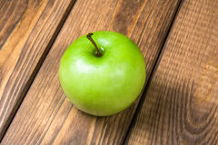 Apple on a wooden background close up. Green apple on a brown wooden background close up Royalty Free Stock Photo