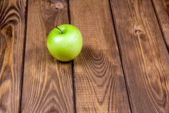 Apple on a wooden background. Green apple on a brown wooden background Stock Images