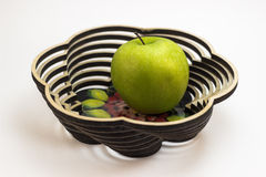 An apple in the wooden dish. An apple in the painted wooden dish Stock Photo