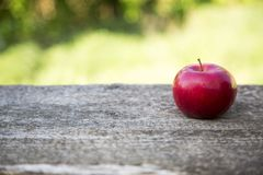 Apple on a wooden table against. Of blurry leaves Royalty Free Stock Photo