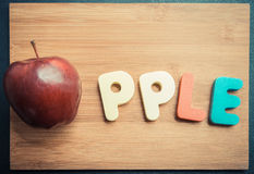 Apple with wooden word on chopping block Stock Photos