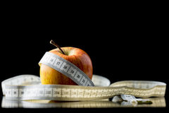 Apple wrapped in a tape measure  over black Royalty Free Stock Photos