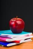 Apple on writing-books Stock Photos