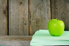 Apple and writing-books on a wooden shelf. Royalty Free Stock Images