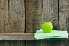 Apple and writing-books on a wooden shelf. Stock Images