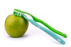 Apple y cepillos de dientes - aislados en el fondo blanco imagen de archivo