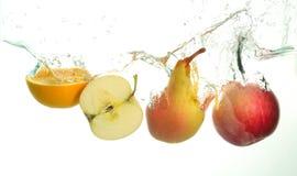 Apple y chapoteo anaranjado de la rebanada y de la pera en agua en el fondo blanco imagenes de archivo