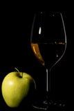 Apple y copa de vino con el jugo en negro Fotografía de archivo