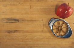 Apple y Corer en una encimera de madera Imágenes de archivo libres de regalías