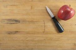 Apple y cuchillo en la tarjeta de corte Imagenes de archivo