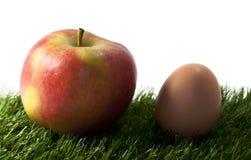 Apple y huevo en hierba verde Foto de archivo