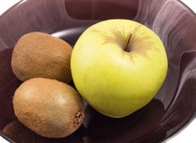 Apple y kiwi en una placa negra Fotos de archivo libres de regalías