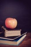 Apple y libros con el fondo de la pizarra Fotos de archivo libres de regalías