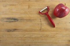 Apple y Peeler en una tarjeta de corte Imagen de archivo libre de regalías