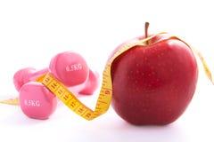 Apple y pesas de gimnasia atados con una cinta de medición. Imagen de archivo libre de regalías