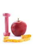 Apple y pesas de gimnasia con una cinta de medición. Imagen de archivo libre de regalías