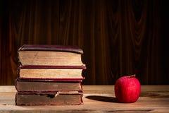 Apple y pila de libros viejos Imagen de archivo