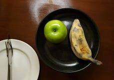 Apple y plátano en la placa Fotografía de archivo libre de regalías