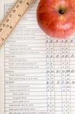 Apple y regla en un boletín de notas de la vendimia Foto de archivo libre de regalías