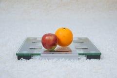 Apple y una naranja están en las escalas Imagenes de archivo