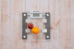 Apple y una naranja están en las escalas Fotos de archivo libres de regalías