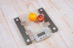 Apple y una naranja están en las escalas Foto de archivo libre de regalías