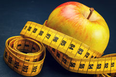 Apple with yellow measuring tape Stock Photo