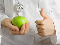 Apple for your health. A green apple is in the hands of doctor Royalty Free Stock Photos
