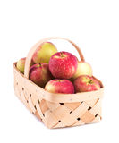 Appleas heaped in a wooden basket,. On white background Stock Photo