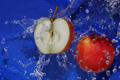 Apples. In a spray of water on a blue background Royalty Free Stock Images