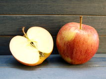 Apples. One and a half apple on a blue wooden background Stock Image