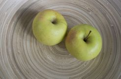 Apples. Two apples on a wooden plate Stock Photos