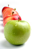 Apples. Neatly stacked  apples on white in front of green Royalty Free Stock Image