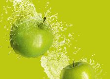 Apples. Two green apples splashed with water on a light green background Royalty Free Stock Photo