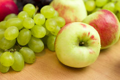 Apples on a background of grapes Stock Photography