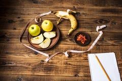 Apples banana carrots notebook and pencil stock photos