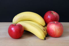 Apples and bananas. Black background Stock Photos