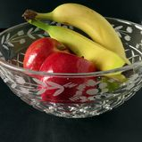 Fruit Bowl. Apples and bananas in a glass, crystal bowl royalty free stock photo