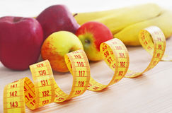 Apples and bananas with tape measure - diet concept Royalty Free Stock Photos