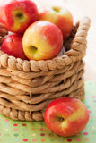 Apples in a basket. Pink lady apples sit in a small basket on top of a polka dot napkin Stock Photography