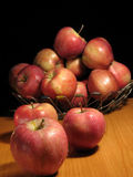 Apples in a basket. A stack of apples in a basket with three of them on the table Stock Images