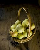 Apples in the basket. Apples are in a wicker basket on the background of wooden boards Royalty Free Stock Images
