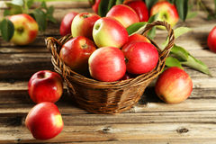Apples in basket on brown wooden background Royalty Free Stock Photo