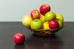 Apples in basket. On brown wooden background Stock Photos