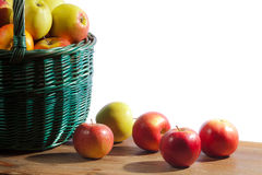 Apples in basket on old plank Stock Photography