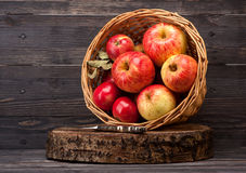 Apples in basket. Red apples in basket on wooden textured board Royalty Free Stock Images