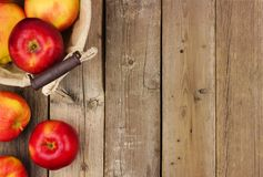 Apples with basket, side border on rustic aged wood Royalty Free Stock Photos